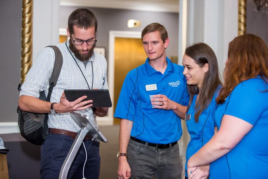 CadmiumCD's Michael Doane, Rachel Vrankin, and Rachel Schmidt, talking with CadmiumCD customer, Preston Reeves of NAFSA, about new event tech.