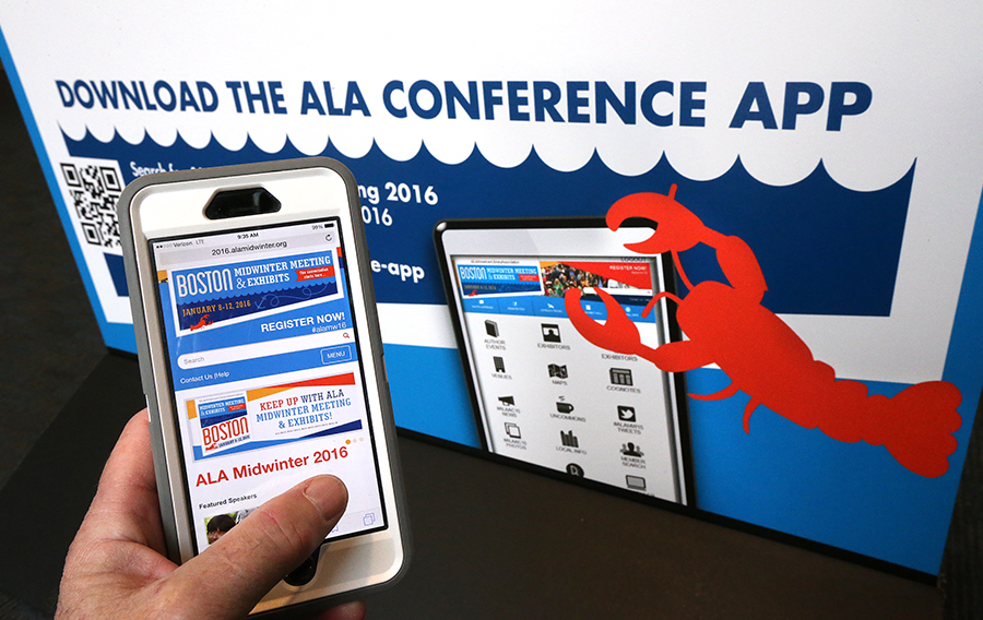An ALA Midwinter 2016 attendee holds an iPhone with the ALA Midwinter app in front of a sign that reads Download the Midwinter App.