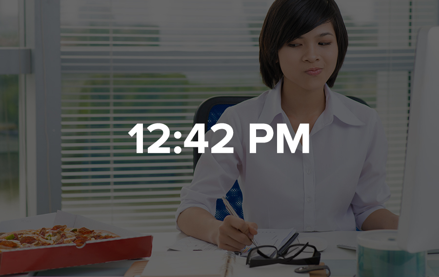 A meeting planner is sitting at her desk working, looking at the pizza sitting next to her, wondering if she should finally take a break and eat something.