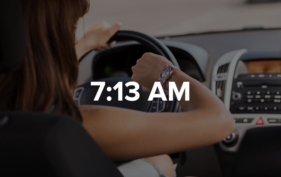 A meeting planner looks at her watch while she's sitting in the car stuck in traffic.